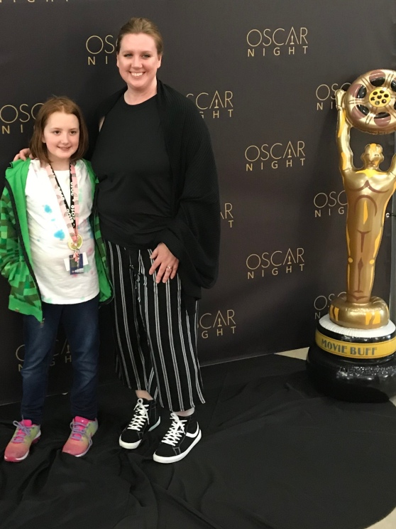 A girl, a mom, and an Oscar in front of an Oscar Night banner.