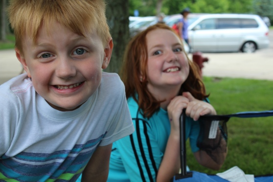 Six year old boy and ten year old girl making goofy faces at a park
