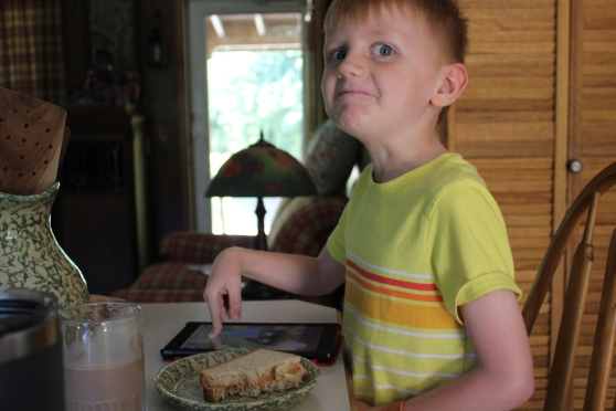 Six year old boy eating lunch, playing on a tablet, and making a goofy face sitting at a kitchen island