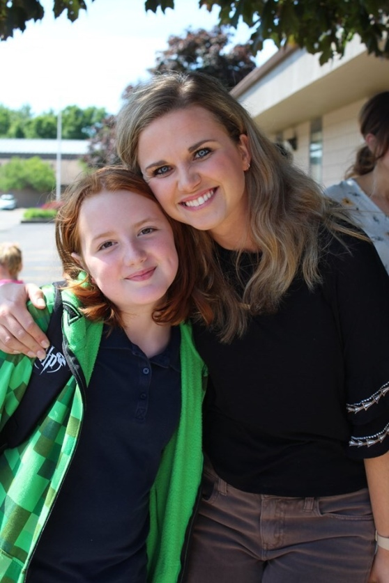 A fourth-turning-fifth grader and her teacher outside the school on the last day of fourth grade