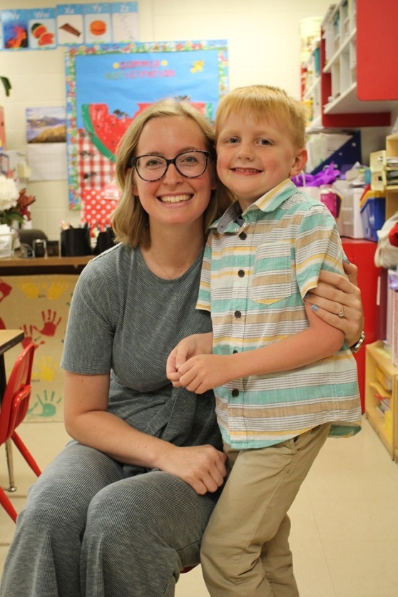 Another teacher and kindergarten graduate in a kindergarten classroom