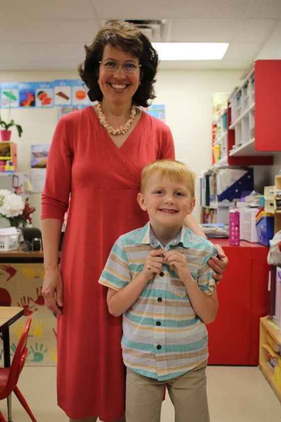 A teacher and kindergarten graduate in a kindergarten classroom