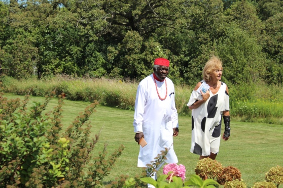 The bride's father, a Nigerian in traditional Igbo garb, walking in a meadow with the groom's aunt, a white woman in a black and white dress.