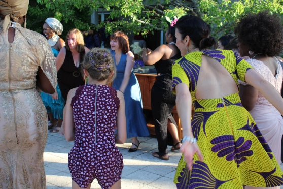 A group of women from several different cultures and a child dancing a traditional Nigerian dance.