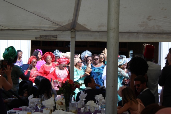 Taken from the back of an outdoor tent, there is a group of women in Igbo dress dancing outside the tent. They are doing a dance to indicate their acceptance of the groom's family for their daughter/cousin—this shows they will not take her away and nullify the wedding. In the foreground are spectators, other wedding guests witnessing the transaction.