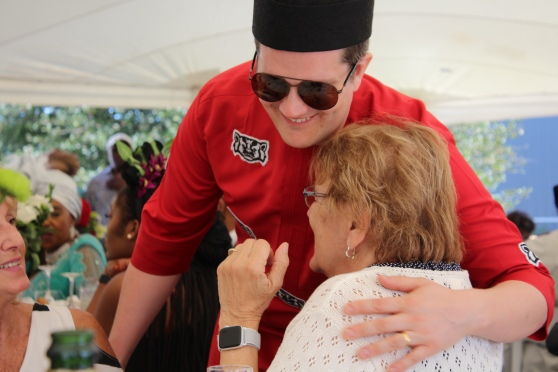 The white groom in an Igbo hat and outfit. The outfit is made from non-traditional material—red with a Wisconsin Badgers logo repeated in a pattern. He is bending over hugging his aunt.
