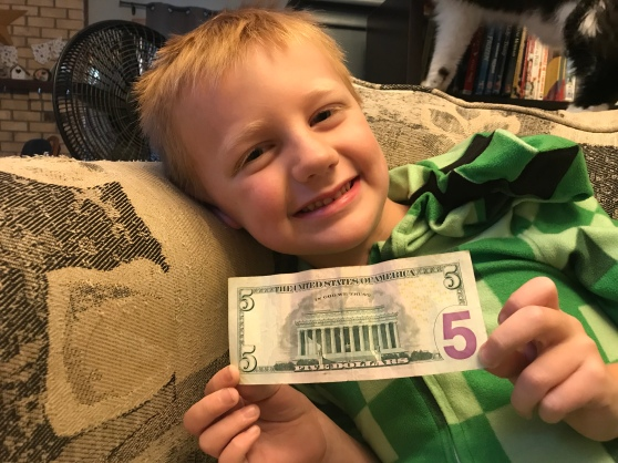 Boy in pajamas holding a $5 bill