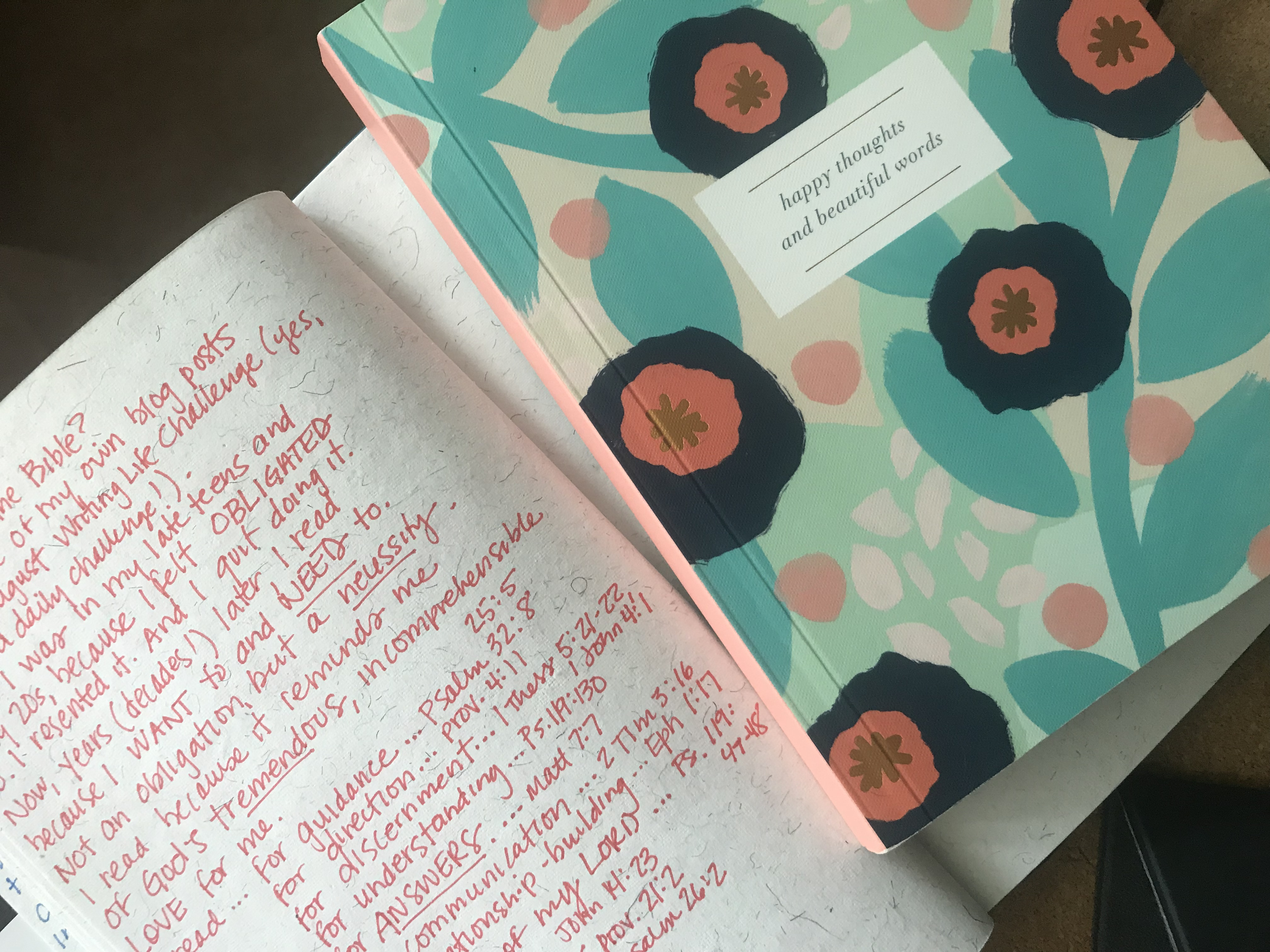 "Journal with a hand-written page listing reasons the writer reads the Bible, and another, closed journal sitting on the opposite page. The closed journal has a floral design and the words ""Happy thoughts and beautiful words"" on the cover."
