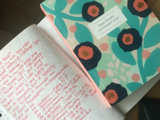 """Journal with a hand-written page listing reasons the writer reads the Bible, and another, closed journal sitting on the opposite page. The closed journal has a floral design and the words """"Happy thoughts and beautiful words"""" on the cover."""