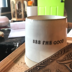 "Stoneware coffee mug that says ""See the good"" with the edge of a leather journal in the foreground"